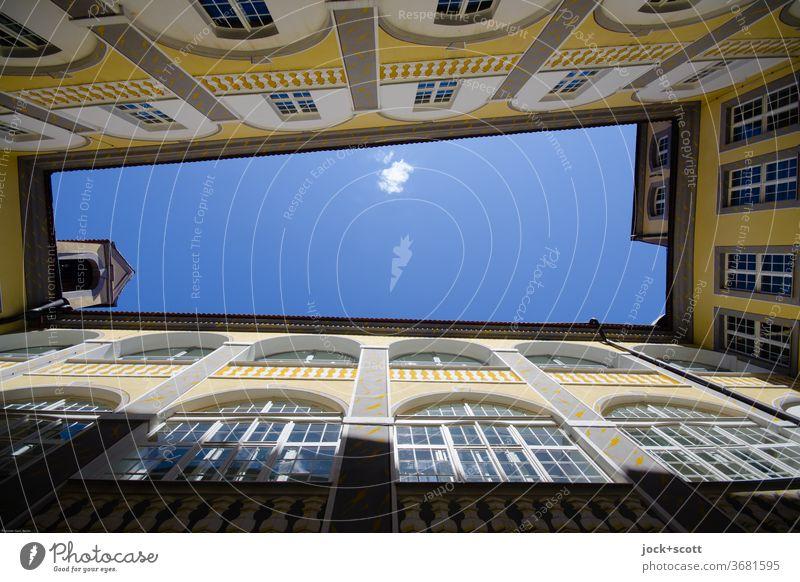 Gegensätze, tiefblauer Himmel mit weißem Tupfer Fassade Hinterhof Symmetrie Stil historisch Schönes Wetter Froschperspektive Innenhof Fenster Architektur