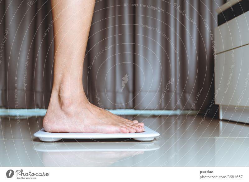 Weibliches Bein steht zu Hause auf weißen Schuppen Magersucht Hintergrund Gleichgewicht Bad schön Schönheit bmi Kalorie Kaukasier Kontrolle Detailaufnahme Gerät