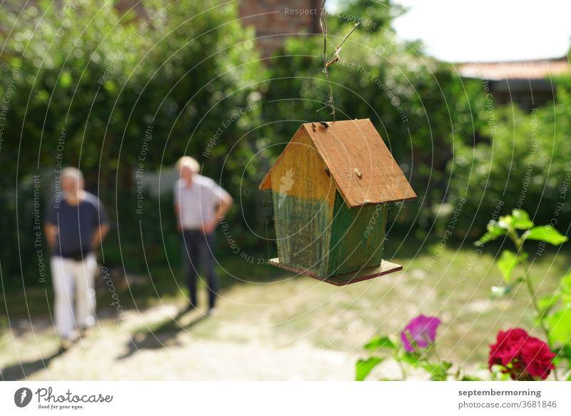 Vogelhäuschen von hinten, hängend Vogelhäuschen aus Holz 2 Männer unscharf im Hintergrund Sommer im Garten rote Blume im Vordergrund Pastelltöne