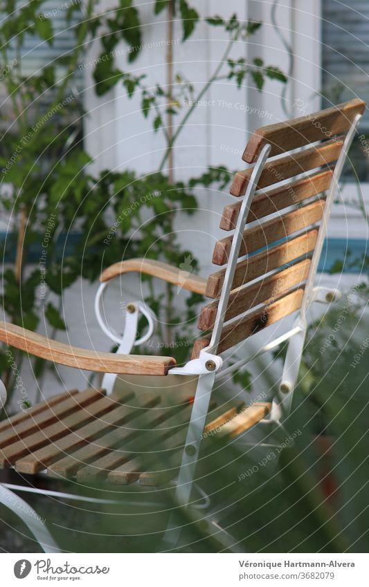 Gartenstuhl aus Holz und Metall mit Tomatenpflanze an Hauswand Stuhl Farbfoto ruhig Möbel Gartenmöbel Ruhepunkt Entspannung im Garten Pause Außenaufnahme