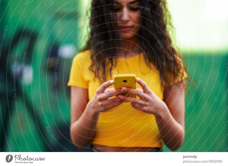 Junge arabische Frau geht auf der Straße mit ihrem Smartphone jung Texten Nachricht Nahaufnahme Tippen gelb copyspace Mädchen Aufnahme Frisur attraktiv schön