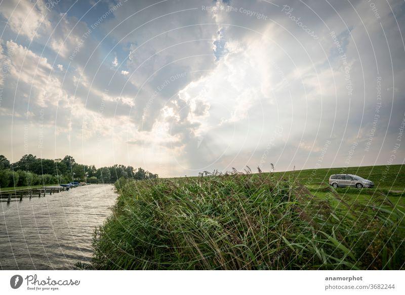 Kanal mit Schilf im Gegenlicht hinter dem Ijsselmeerdeich Wasser Wolkenhimmel Gegnlicht Lichtstrahlen godrays Farbfoto Menschenleer Außenaufnahme Himmel Tag