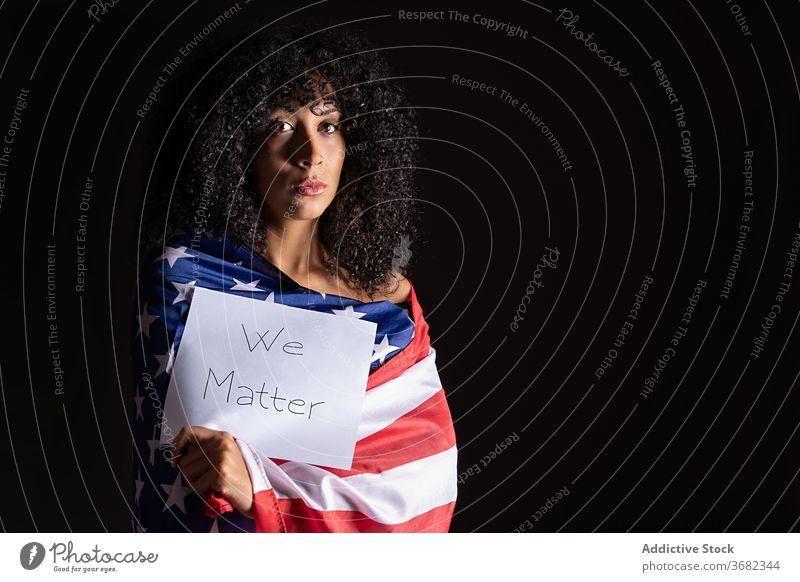 Traurige und besorgte afrikanische Frau trägt eine patriotische amerikanische Flagge Aktivismus Afrikanisch Afro-Look nachdenklich Amerikaner USA umhüllen schön