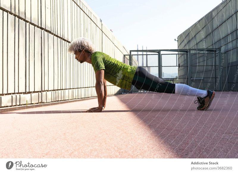 Afroamerikanischer Sportler macht Liegestütze auf der Straße Großstadt Fitness Training hochschieben Gehege Übung passen physisch männlich Wellness stark