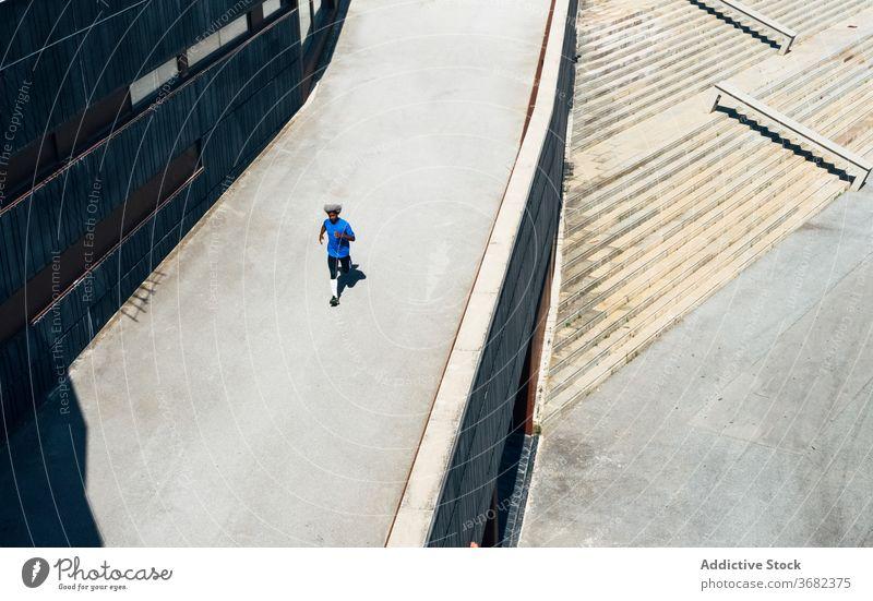 Ethnischer Sportler läuft auf der Straße laufen Weg Training Fitness Gebäude modern Großstadt Sportbekleidung urban männlich schwarz Afroamerikaner ethnisch