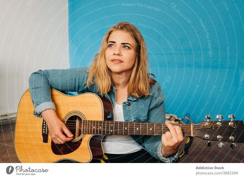 Nachdenkliche Frau spielt Gitarre auf dem Boden spielen nachdenklich Musiker Stock Wand akustisch jung lässig Instrument sitzen Gesang Melodie Denken besinnlich
