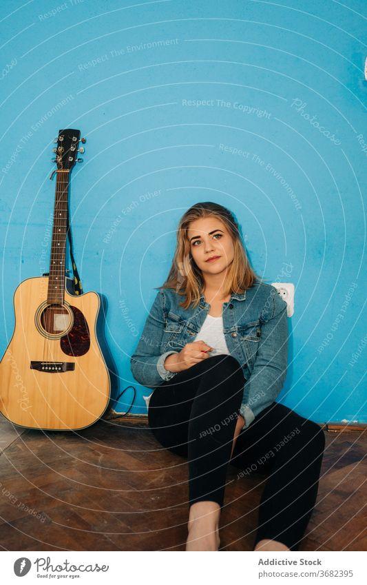 Nachdenkliche Frau sitzt in der Nähe von Gitarre auf dem Boden spielen nachdenklich Musiker Stock Wand akustisch jung lässig Instrument sitzen Gesang Melodie