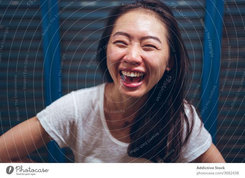 Fröhliche junge ethnische Frau, die in die Kamera lacht heiter Lachen Glück Freude Spaß haben aufgeregt positiv Porträt asiatisch froh lässig Optimist modern