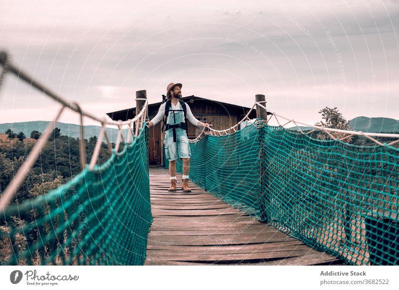 Reisender Mann zu Fuß entlang Holzsteg Suspension Steg Tourist Spaziergang Rucksack bewundern Landschaft hölzern Urlaub männlich Abenteuer Ausflug Tourismus