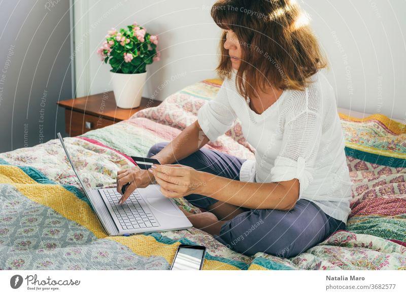 Frau, die mit Karte bezahlt, um von zu Hause aus mit dem Laptop auf dem Bett sitzend online einzukaufen. heimwärts Postkarte bezahlen Kauf mittleres Alter