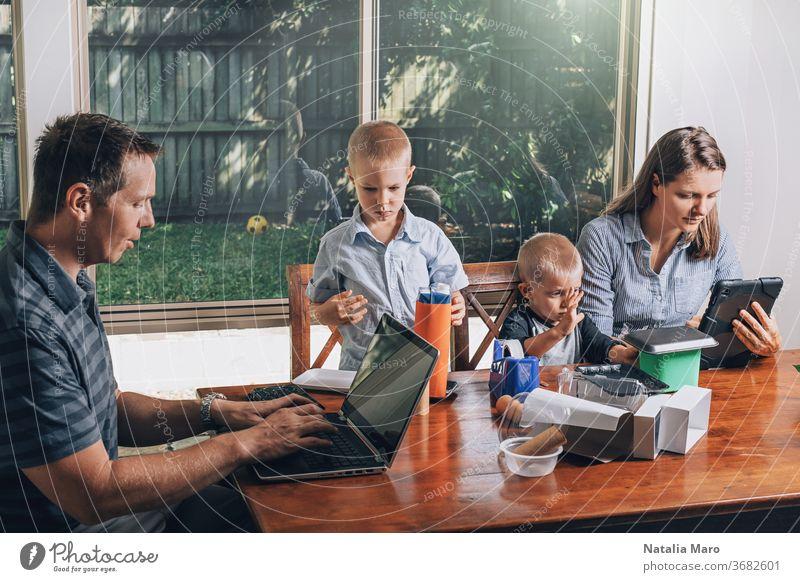 Konzept der Arbeit von zu Hause und der Familienerziehung zu Hause. Eltern und zwei Söhne sitzen am Schreibtisch. heimwärts Laptop Kind Büro wiederverwertet