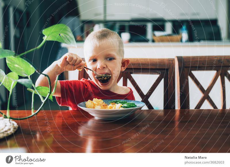Süßes Kind, Vorschulkind, isst Gemüse zum Mittagessen im Speisesaal Kindheit Lebensmittel Glück Löffel veggies Mund Salatgurke Kartoffel hungrig Freude