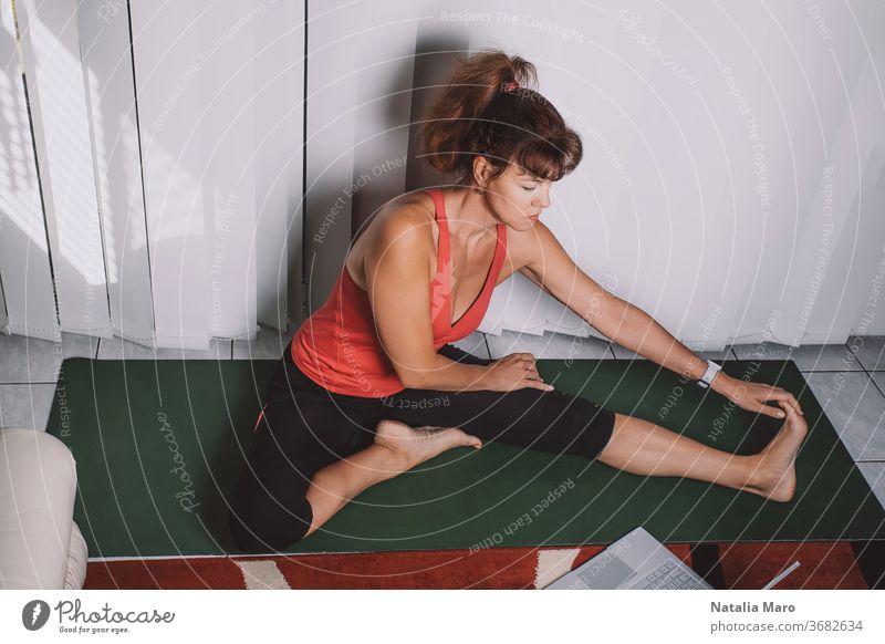 Attraktive Frau mittleren Alters, die zu Hause Yoga macht und online Unterricht hat. Bleiben Sie während der Quarantäneversieglung gesund heimwärts Frauen