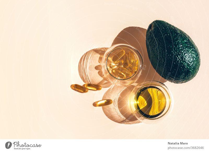Kapseln Fischöl Omega-3 in Glasbechern und eine Avocado mit einem Schatten im Sonnenlicht auf dem beigen Hintergrund. Apotheke Tablette Erdöl Ergänzungsmittel