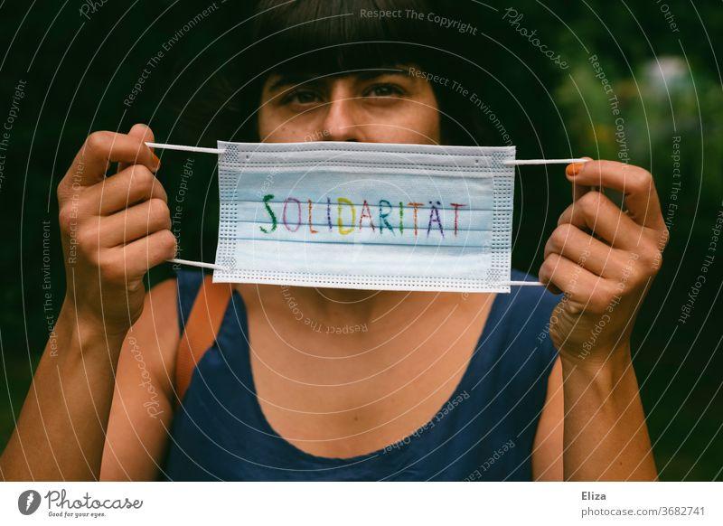 Ein Mundschutz auf dem in bunten Buchstaben das Wort Solidarität steht. Pro Maskenpflicht und Masken tragen zum Schutz aller während der Corona Pandemie.
