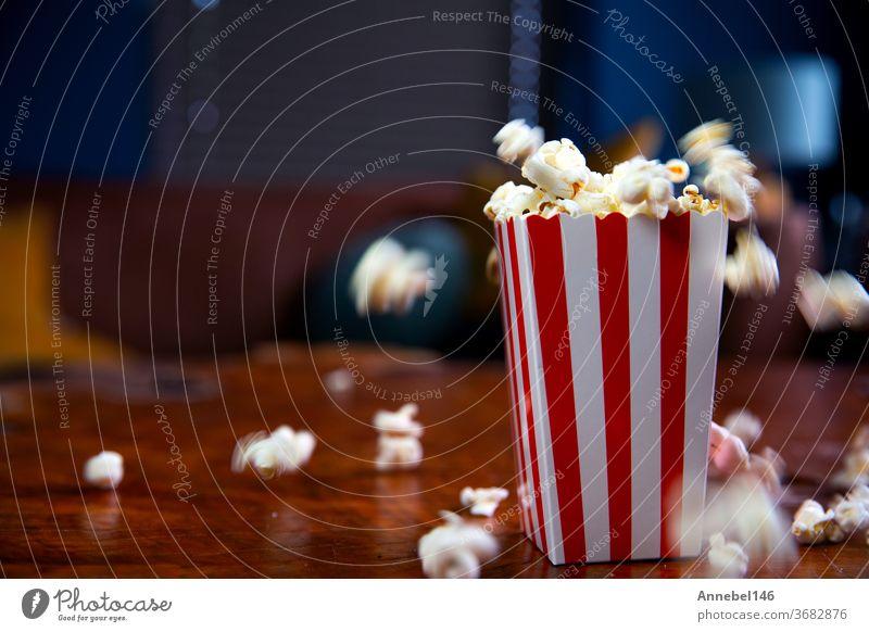 Popcorn fliegt aus Pappkarton. rot-weiß gestreifter Popcorn-Eimer mit fliegendem Popcorn im Wohnzimmer, Film- oder Kinokonzept Popkorn Mais Kasten Snack fallend