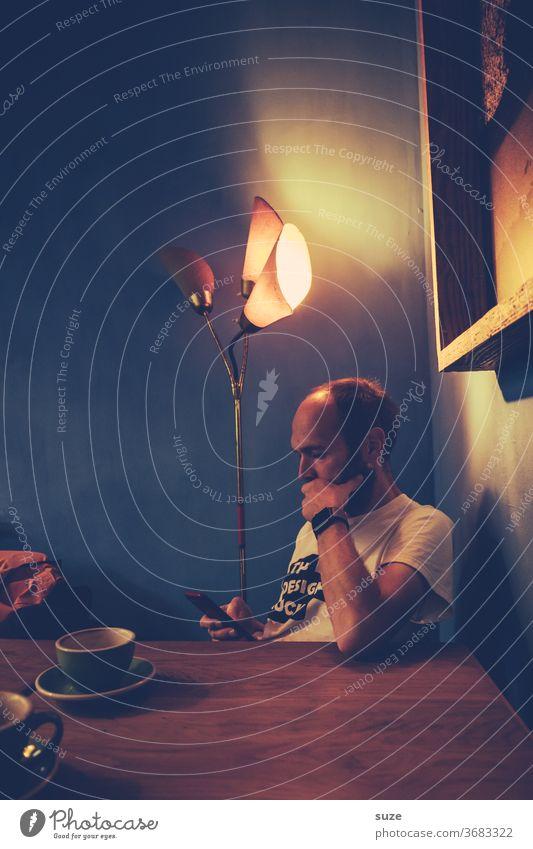 Systemupdate zum Feierabend im Dämmerlicht Mann Maennlich Tag Café Kaffee Kaffeetrinken Heißgetränk Getränk Innenaufnahme Farbfoto Handy überlegen Gedanken
