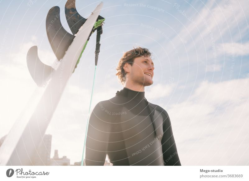 Surfer, der am Strand neben seinem Surfbrett steht. Mann Brandung Wasser Sport Surfen MEER Meer im Freien sportlich Küstenlinie Wellen Hintergrund Abenteuer