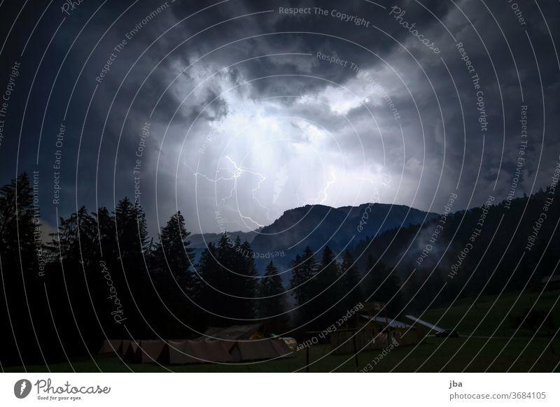 Gewitter über dem Zeltlager Blitz Wolke Nacht hell dunkel Zeltplatz Wald Berggrat imposant Gewitternacht