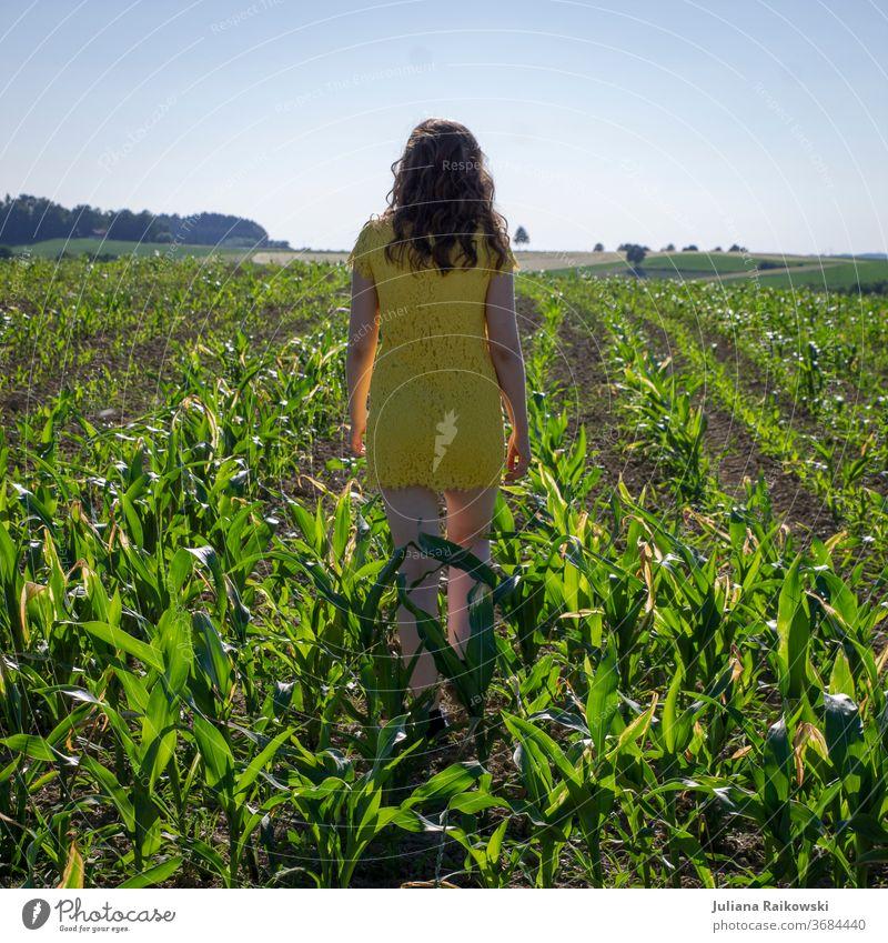 Mädchen in gelbem Kleid in einem Maisfeld Feld Sommer Landwirtschaft Pflanze Natur grün Nutzpflanze Umwelt Außenaufnahme Himmel Farbfoto Landschaft