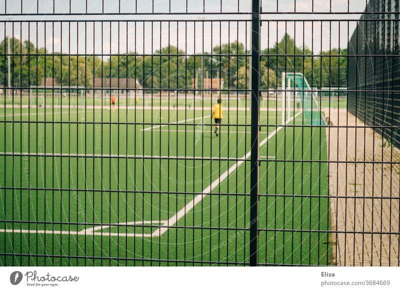 Junger Fussballer auf einem Fußballfeld hinter einem Zaun Fussballfeld Fußballplatz Sport Spielen Sportplatz Ballsport Freizeit & Hobby Gitter Sportstätten Tor