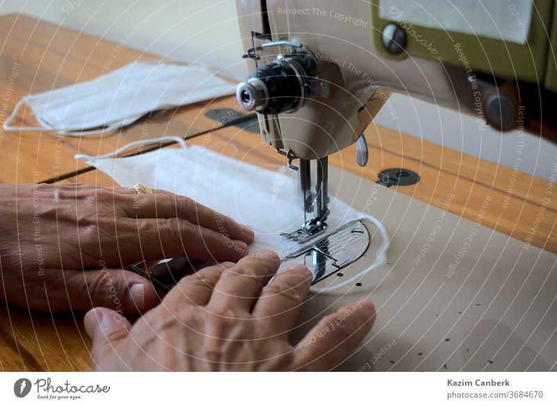 Nahaufnahme einer Frau, die mit einer Nähmaschine eine chirurgische Maske herstellt Hände abschließen Nähen Ring Hausfrau Gesichtsbehandlung Mundschutz Korona