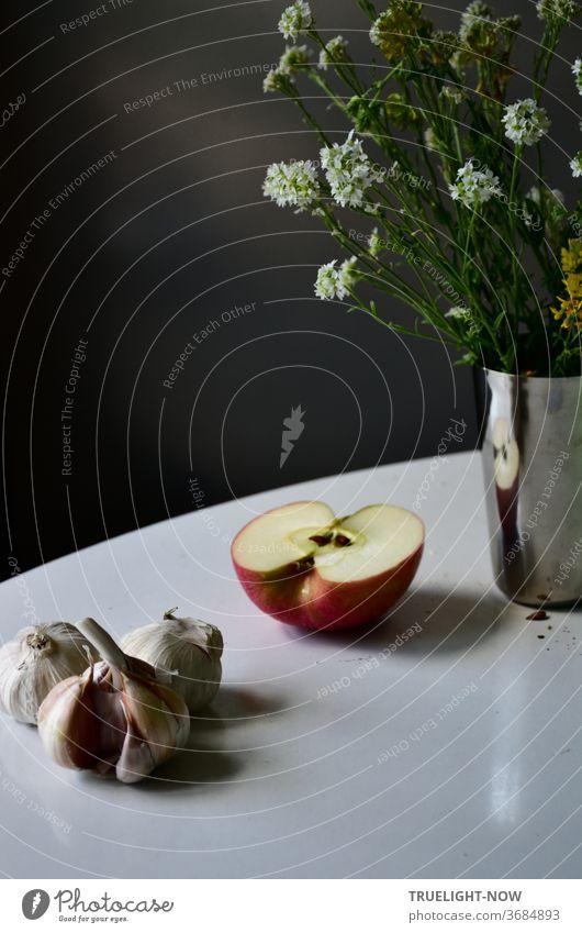 Weißer runder Tisch vor dunklem Hintergrund mit einem Stillleben aus Knoblauch, halbem Apfel und chromglänzender kleiner Metallvase in der ein Strauß Wiesenblumen mit kleinen weißen Blüten und grünen Blättern steht