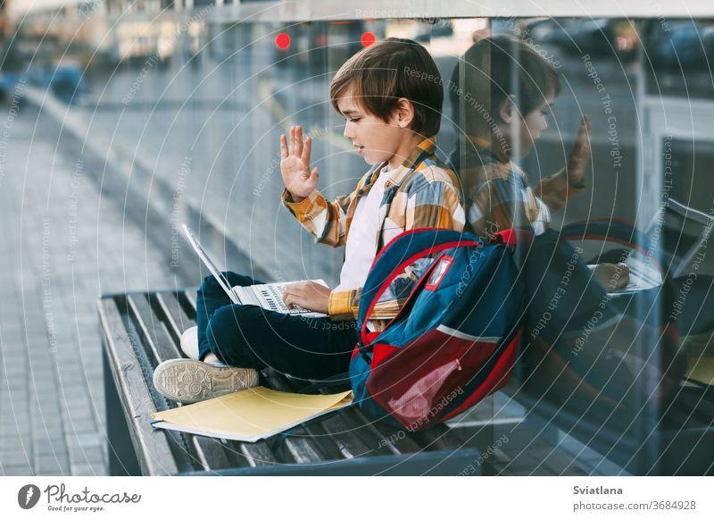 Ein süßer Junge sitzt auf einer Bank, hält einen Laptop auf seinem Schoß, neben einem Rucksack. Der Junge kommuniziert mit Freunden über den Computer und winkt ihnen zu. Bildung, Technologie, Fernunterricht