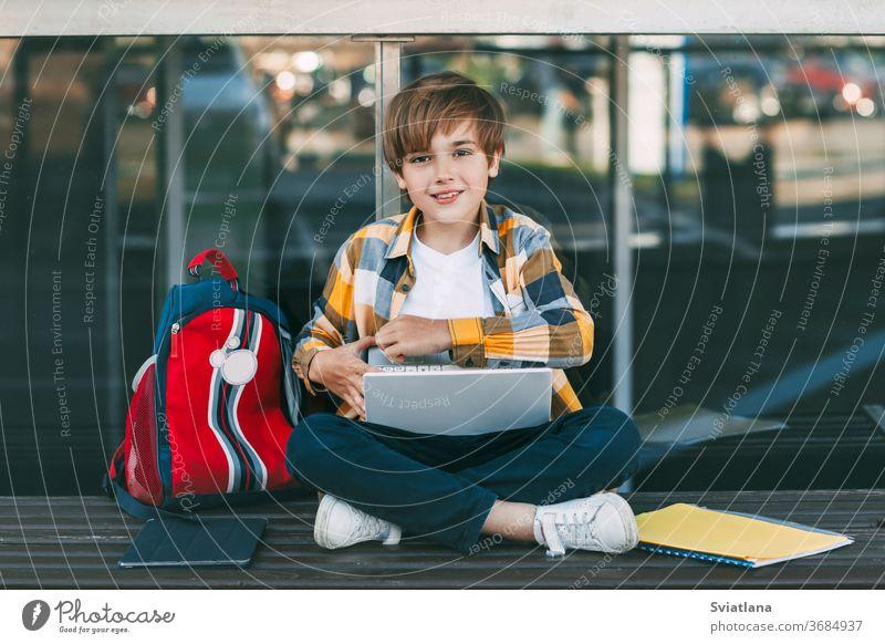 Ein süßer Junge in einem karierten Hemd sitzt auf einer Bank mit einem Laptop und tippt auf der Tastatur, neben einem Rucksack. Der Schüler bereitet sich auf den Unterricht im Freien vor.