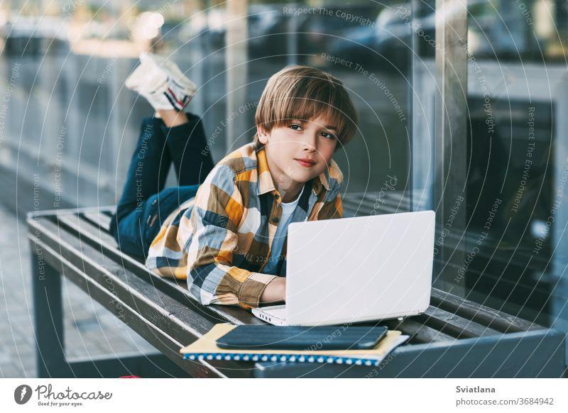 Ein lächelnder Junge liegt auf einer Bank und bereitet sich neben einem Rucksack auf den Schulunterricht vor. Der Junge ruht sich zwischen den Unterrichtsstunden aus. Soziale Distanz. Fernunterricht, Bildung, moderne Technologien