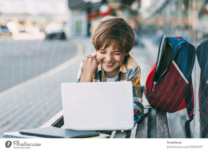 Ein fröhlicher Junge liegt auf einer Holzbank und arbeitet an einem Laptop, neben einem Rucksack. Ein Schüler bereitet sich mit Hilfe des Internets auf den Schulunterricht vor. Soziale Distanz. Fernunterricht