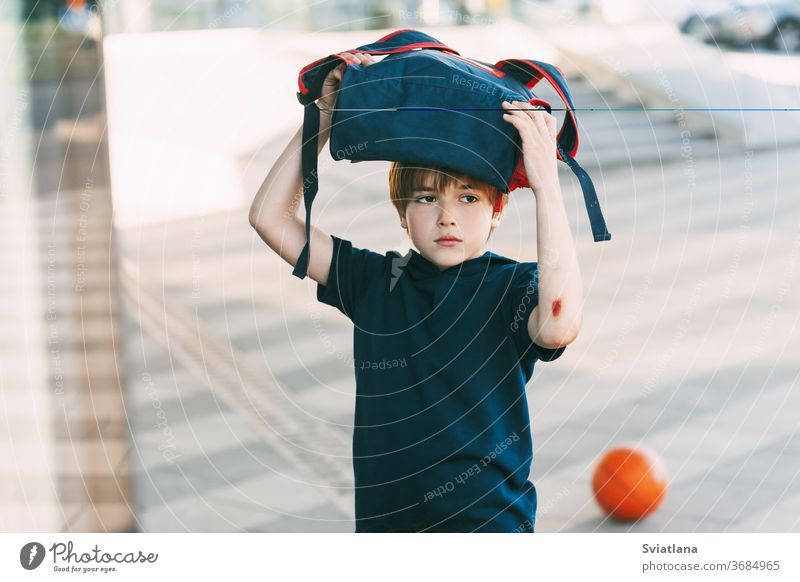 Ein müder Junge in Sportuniform und mit einer Wunde am Arm kehrt nach dem Basketballtraining nach Hause zurück. Bildung, Erziehung, Sportunterricht Rucksack