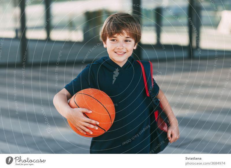 Porträt eines schönen Jungen in Sportuniform mit Rucksack und Basketball. Der Junge lächelt und hält den Ball in seinen Händen. Training, Erziehung, Sportunterricht