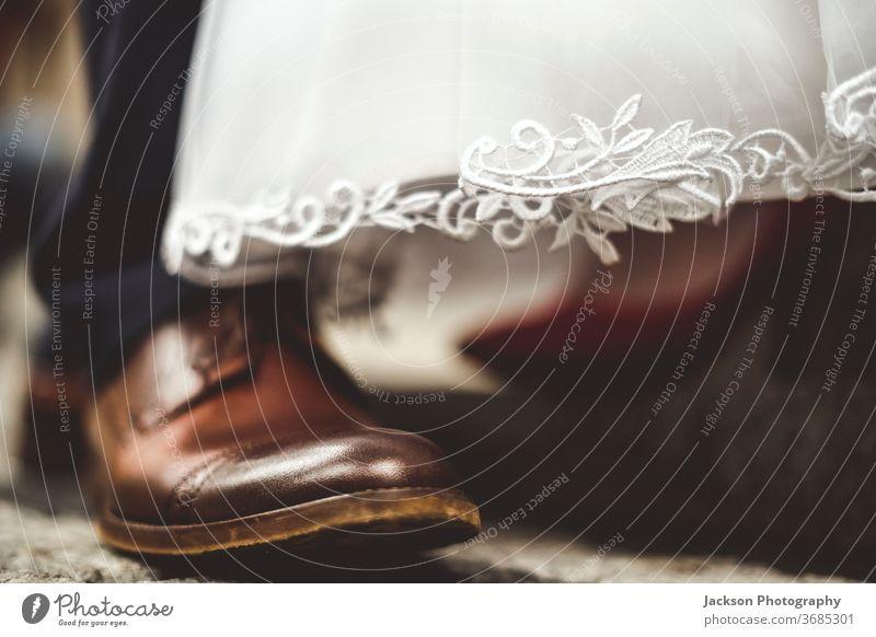 Nahaufnahme der Schuhe von Braut und Bräutigam. striegeln Hochzeit Mode sexy Fuß rot Treppe im Freien weiß Kleid Brautkleid modisch Bekleidung Fersen