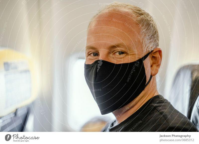 Im Flugzeug sitzender Mann mit schützender Gesichtsmaske Mundschutz Ebene Reisender Prävention Krankheit Menschen Virus Coronavirus covid-19 Glück positiv
