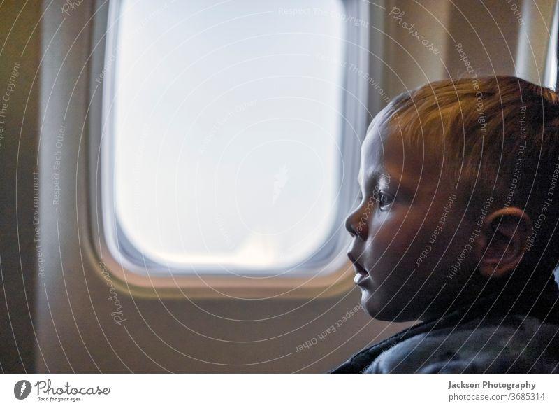 Ernsthaftes Kleinkind sitzt im Flugzeug neben dem Fenster Kind ernst reisen Junge sitzen Textfreiraum ungewiss furchtbar neugierig klein Kaukasier Gesicht