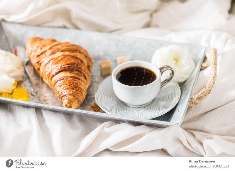 Frisches Croissant, Tasse Kaffee und Hahnenfußblüten. Frühstück im Bett Morgen Romantik Gebäck weiß Tisch Ranunculus Blumen trinken Tablett Espresso süß