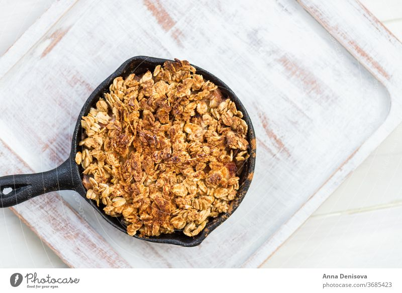 Hausgemachter gekochter Rhabarber und Apfelstreusel mit Haferflocken bröckeln Beeren Gesundheit Frucht Kuchen Schuster Lebensmittel Erdbeeren hölzern Pfanne süß