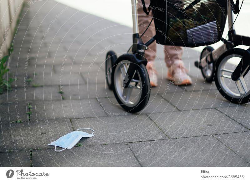 Eine Frau mit Behinderung geht mit ihrem Rollator, daneben ein am Boden liegender Mundschutz. Maskenpflicht um Risikopatienten zu schützen. Risikopatientin