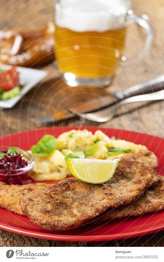 Wiener Schnitzel mit Kartoffelsalat auf dem Teller wiener schnitzel Kalbsschnitzel Petersilie Zitronenscheibe Portion knusprig braun paniert Besteck