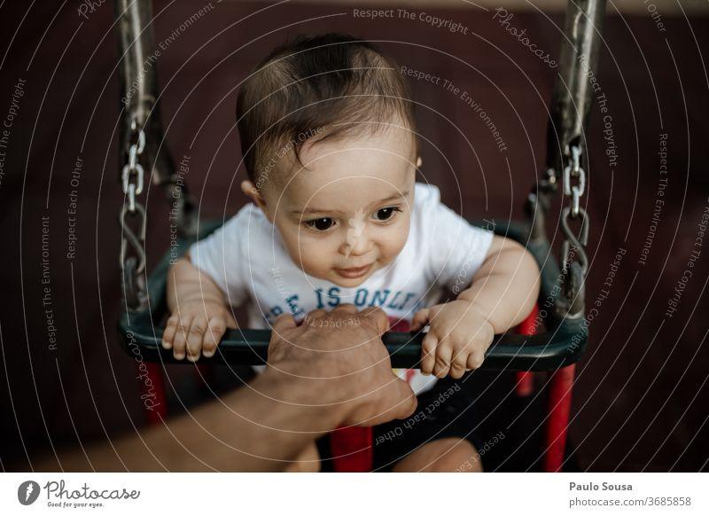 Vater hält Baby auf der Schaukel pendeln Spielplatz Zusammensein Zusammengehörigkeitsgefühl Vaterschaft Säuglingsalter Sichtweise Lifestyle Familie Menschen