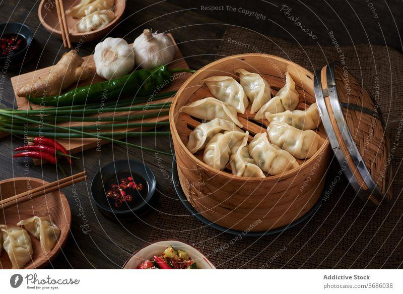Chinesische gedämpfte Knödel xiaolongbao jiaozi chinesisches Essen Lebensmittel lecker Holz dunkle Speisen Gemüse Salatbeilage Salatgurke Verdunstung