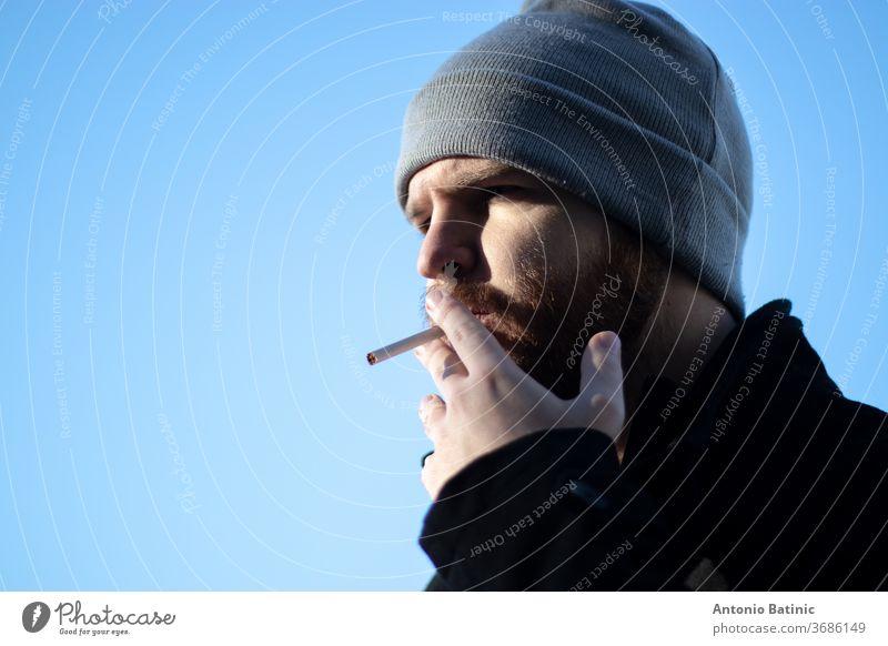 Kaukasischer bärtiger Mann mit einer Mütze, der eine Zigarette in der Hand hält, raues Sonnenlicht mit starken Schatten.  Enge Aufnahme mit blauem Himmelshintergrund