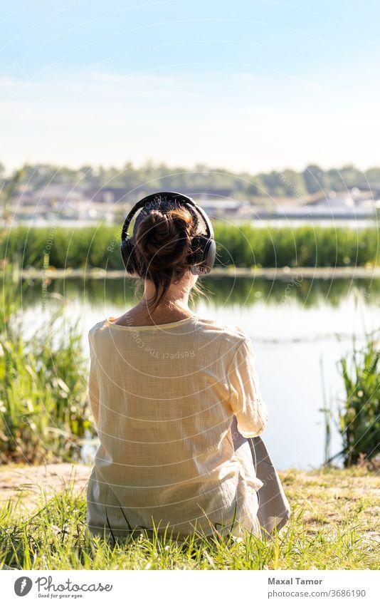 Frau mit Kopfhörern meditiert, sie sitzt vor dem Fluss, kurz nach Sonnenaufgang. Erwachsener schön Schönheit Körper Windstille Kaukasier Konzentration Energie