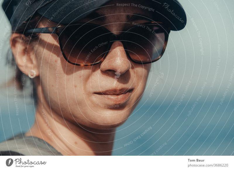 Portrait einer Frau mir Basecap und Sonnenbrille Porträt basecap sonnenbrille mütze Blick in die Kamera Mensch Erwachsene Farbfoto Mütze Außenaufnahme feminin