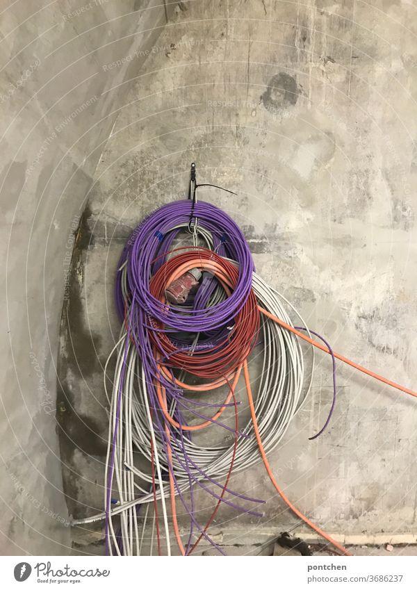 Bunte Kabel hängen aufgerollt an einer Betonwand . Kabelsalat baustelle kabelsalat leitungen rollen lila bunt Technik & Technologie Energiewirtschaft
