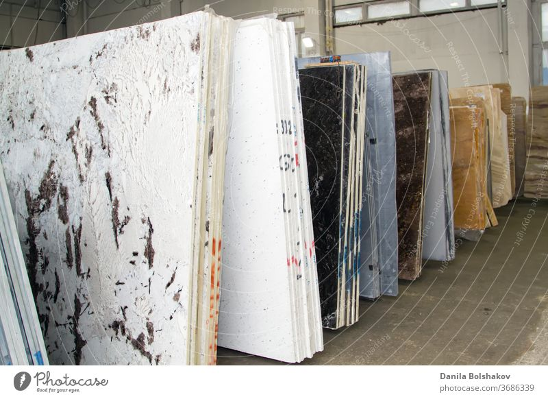 Bunte Marmorplatten im Ausstellungsraum des Geschäfts. Granitplatten werden für den Verkauf im Lagerhof vorbereitet. Perlmutt Arbeitsplatte Brühe Industrie
