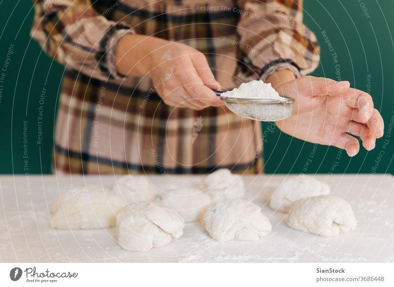 Frau streut Mehl zu handgemachten Teigstücken für Brot, hausgemachtes Kochen. Teigwaren handgefertigt Streusel Hände Essen zubereiten weiß Person Pulver