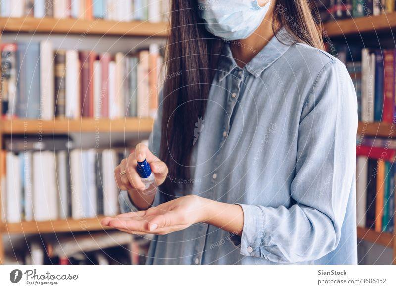 Coronavirus-Konzept. Mädchen zu Hause besprüht ihre Hände zum Schutz vor dem Coronavirus mit einem Antiseptikum. Weltweiter Aufruf, zu Hause zu bleiben. COVID