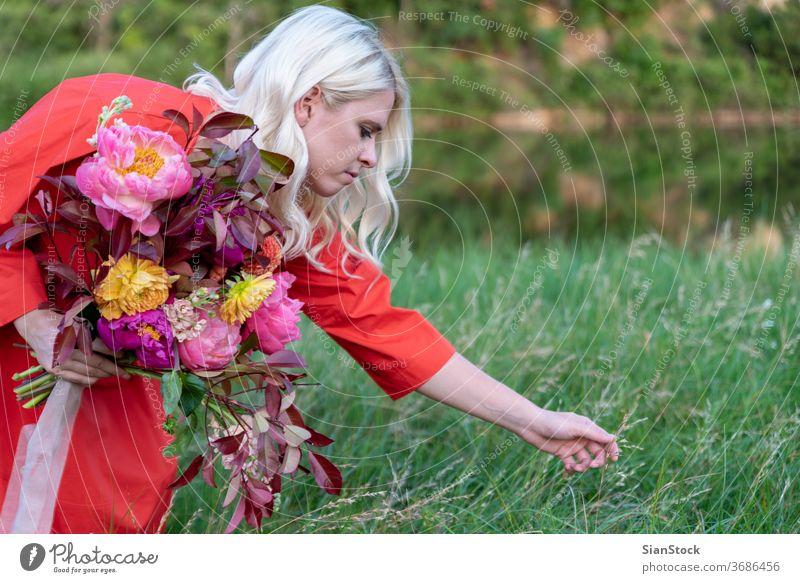 Blonde Frau mit Blumen auf dem Land. Porträt Begeisterung Tag Morgen Lifestyle Fröhlichkeit Farbfoto Blüte Euphorie schön Mensch Innenbereich Dekor Model